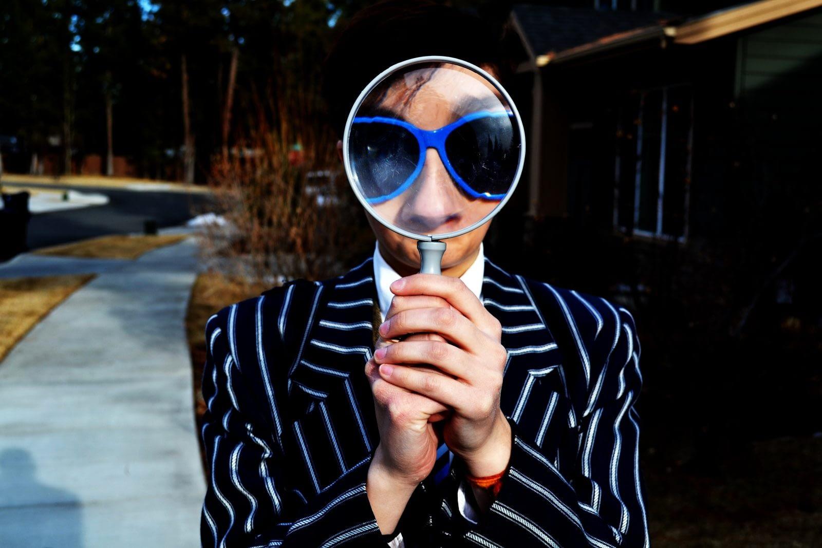 Mann mit blauer Brille und großer Lupe